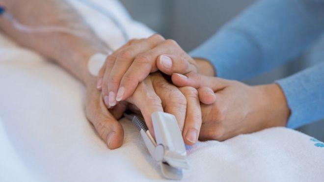Manos de mujer joven sosteniendo las de un hombre mayor enfermo
