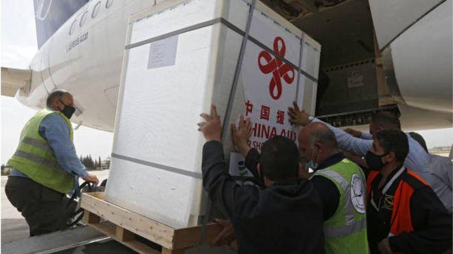 عمال ينزلون صناديق تحوي لقاح سينوفارم الصيني من إحدى الطائرات في مطار دمشق الدولي تبرعت بها الصين لسوريا