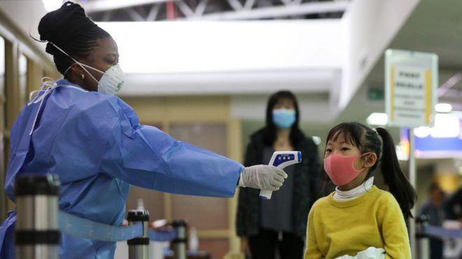 A Kenyan health worker (L) screens a passenger wearing face mask after they arrived from China, at Jomo Kenyatta International Airport in Nairobi, Kenya, 29 January 2020