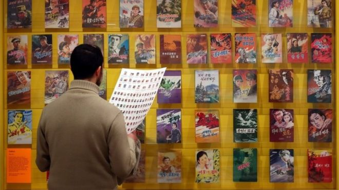 A man looks at comic book covers.