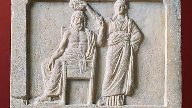 Relevo mostra a democracia coroando Demos, o povo de Atenas