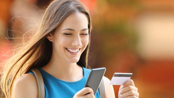 Cliente con celular y tarjeta de crédito.