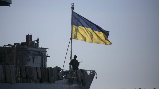 A Ukrainian naval ship, with a soldier standing in front of a Ukrainian flag