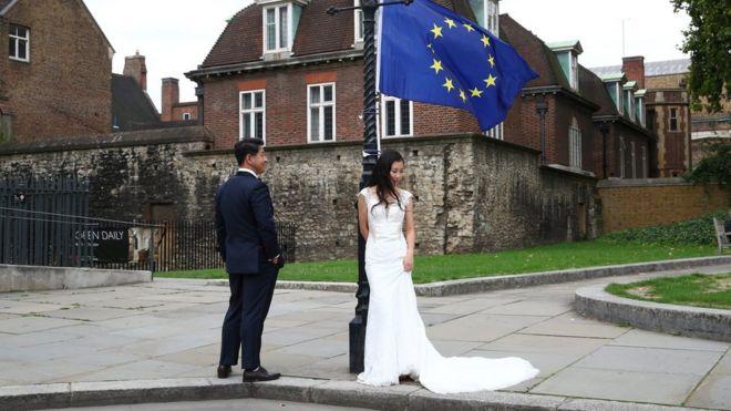 一對中國的新人在倫敦一處抗議脫歐者放置的歐盟旗幟下拍攝婚紗照