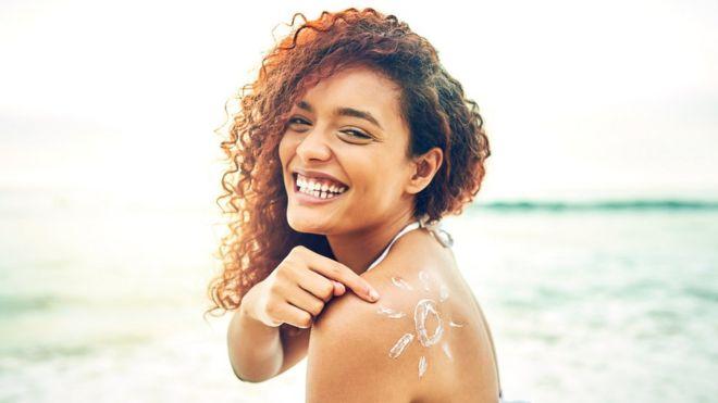 Pessoa com filtro solar na praia
