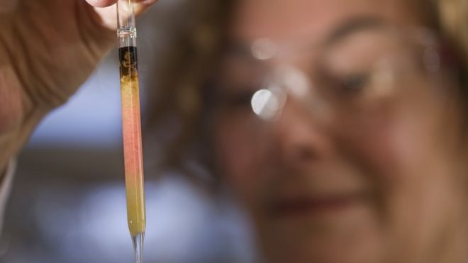 A scientist holds up a vial of the pigment