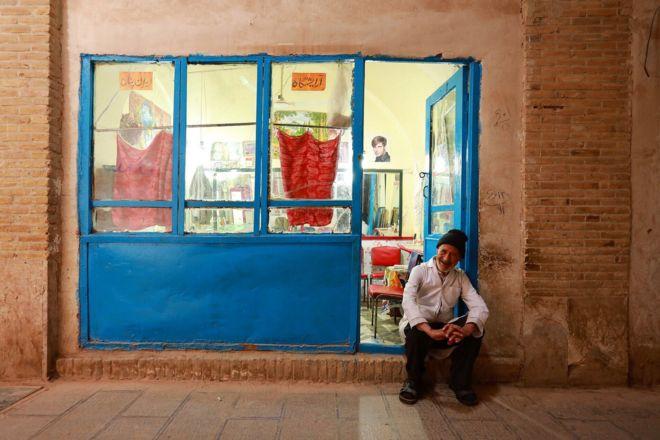 بازار کرمان؛ علی - ۸۰ ساله - علیرغم بیماری پارکیسنون به کار آرایشگری مشغول است