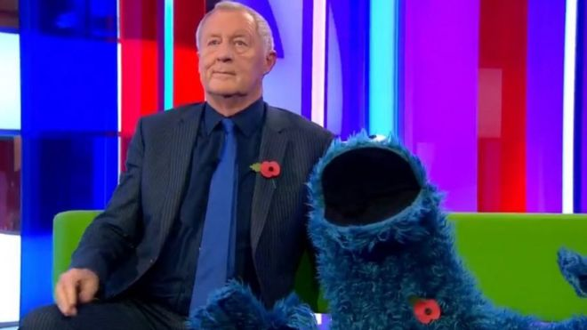 A picture of the Cookie Monster character on the One Show, wearing a poppy
