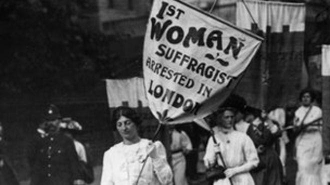 Марш протеста женщин-суфражисток в Лондоне с участием полиции.Знамя ведущих женщин гласит: «1-я женщина-суфражистка арестована в Лондоне»