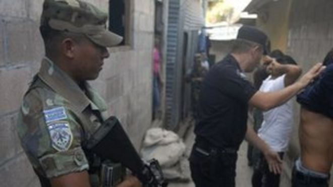 Солдат стоит на страже, пока полиция ищет наркотики и оружие в Сан-Сальвадоре, столице Сальвадора, в январе 2012 года