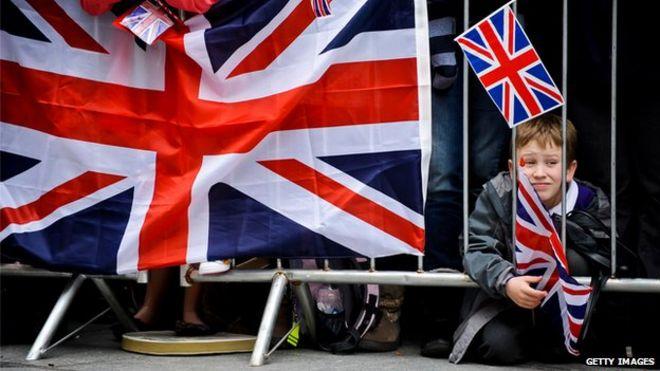Молодой мальчик ждет в толпе с флагом до прибытия королевы Елизаветы II для посещения центра города Эксетер 02 мая 2012 года