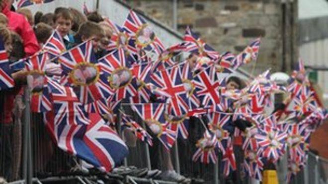 Толпа размахивает Юнион Флаги