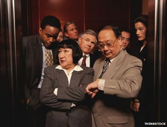 people in elevator. eight people squeezed in a lift elevator