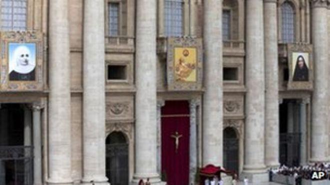 Гобелены (слева), на которых изображены Лаура ди Санта Катерина да Сиена Монтойя из Колумбии, Антонио Примальдо и его спутники, также известные как Мученики Отранто, и Мария Гваделупа Гарсия Завала из Мексики висят на балконах на площади Святого Петра в Ватикане