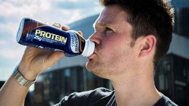 Мужчина пьет протеиновый коктейль