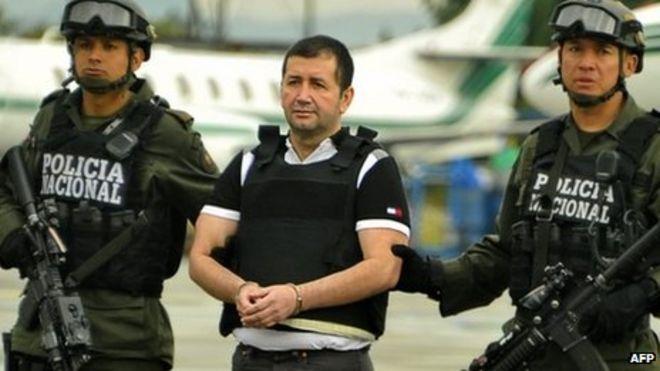 Колумбийский торговец наркотиками Даниэль Баррера сопровождается полицейскими перед депортацией в США 9 июля в Боготе