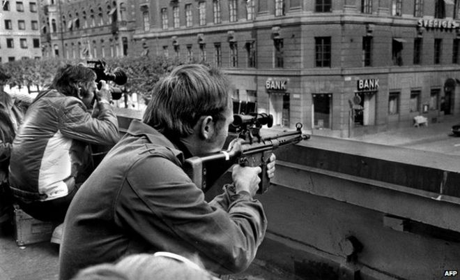 Two policemen hold guns, poised opposite a Kreditbanken building