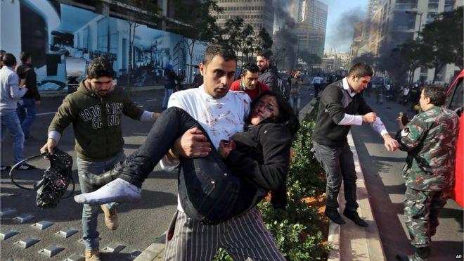 Um libanês carrega uma mulher ferida no local de uma explosão em Beirute, Líbano, (27 de dezembro de 2013)