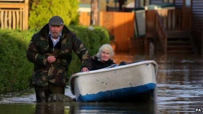 Мужчина пробирается через воду, тянет лодку, в которой сидит женщина