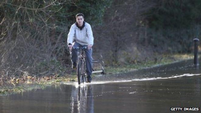Мужчина едет на велосипеде через паводковые воды