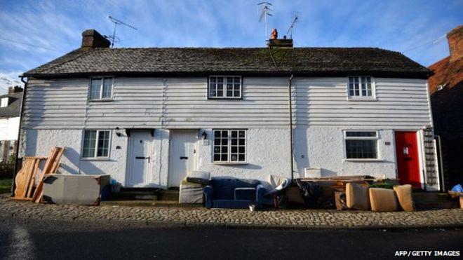 Поврежденная наводнением мебель накапливается возле домов в деревне Ялдинг в графстве Кент на юге Англии