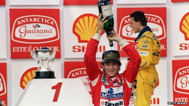 Бразильский гонщик Формулы-1 Айртон Сенна наливает шампанское на себя 28 марта 1993 года, празднуя свою победу в Гран-при Бразилии в Сан-Паулу. Это была 37-я победа Гран-при Сенны, но только вторая его победа в Бразилии.