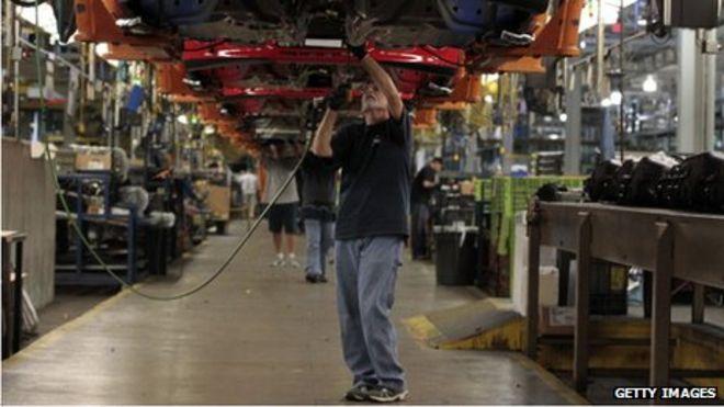 Сотрудник работает под автомобилем Ford Motor Co. Focus в Уэйне, штат Мичиган, 7 октября 2013 г.