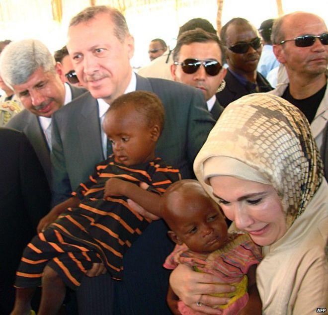 Премьер-министр Турции Реджеп Тайип Эрдоган и его жена Эмине держат детей во время их посещения лагеря беженцев в Сомали, август 2011 года