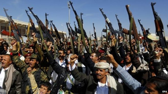 Tribal gunmen loyal to the Shiite Houthi Group shout slogans and hold weapons apparently to show