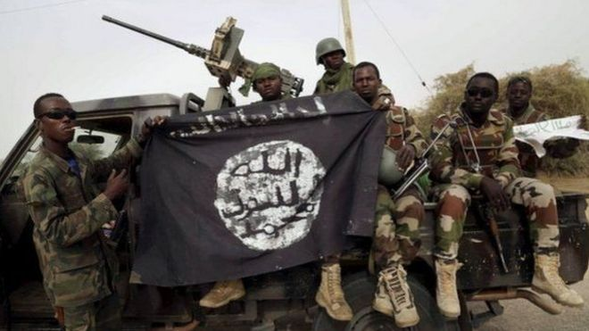 Nigerian soldiers displaying a Boko Haram black flag
