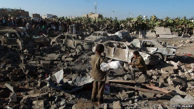 Yemen crisis. Yemenis stand at the site of a Saudi air strike against Huthi rebels near Sanaa Airport