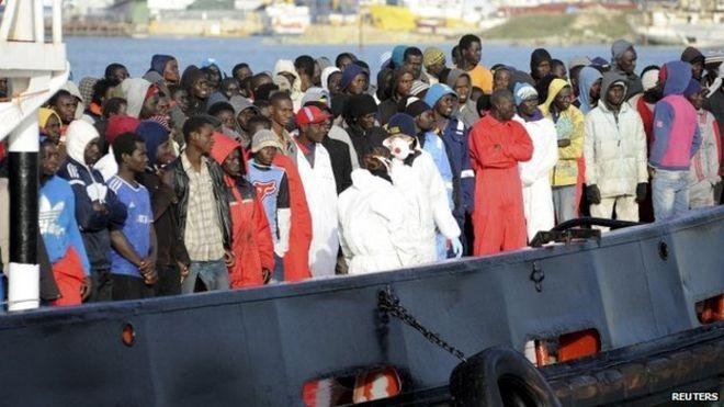 Мигранты ждут, чтобы сойти с буксира в сицилийской гавани Трапани, 17 апреля 2015 г.
