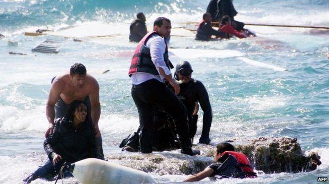 Местные жители и спасатели помогают женщине-мигранту после того, как лодка с мигрантами затонула у острова Родос, юго-восточная Греция, 20 апреля 2015 года