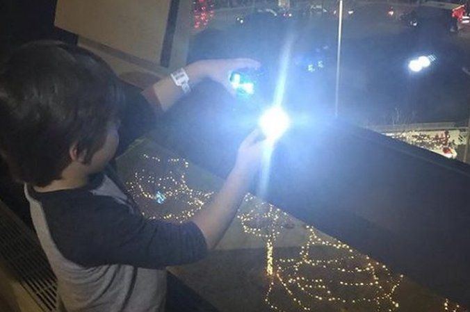 Graham shines his flashlight through his hospital window, while lights twinkle from below