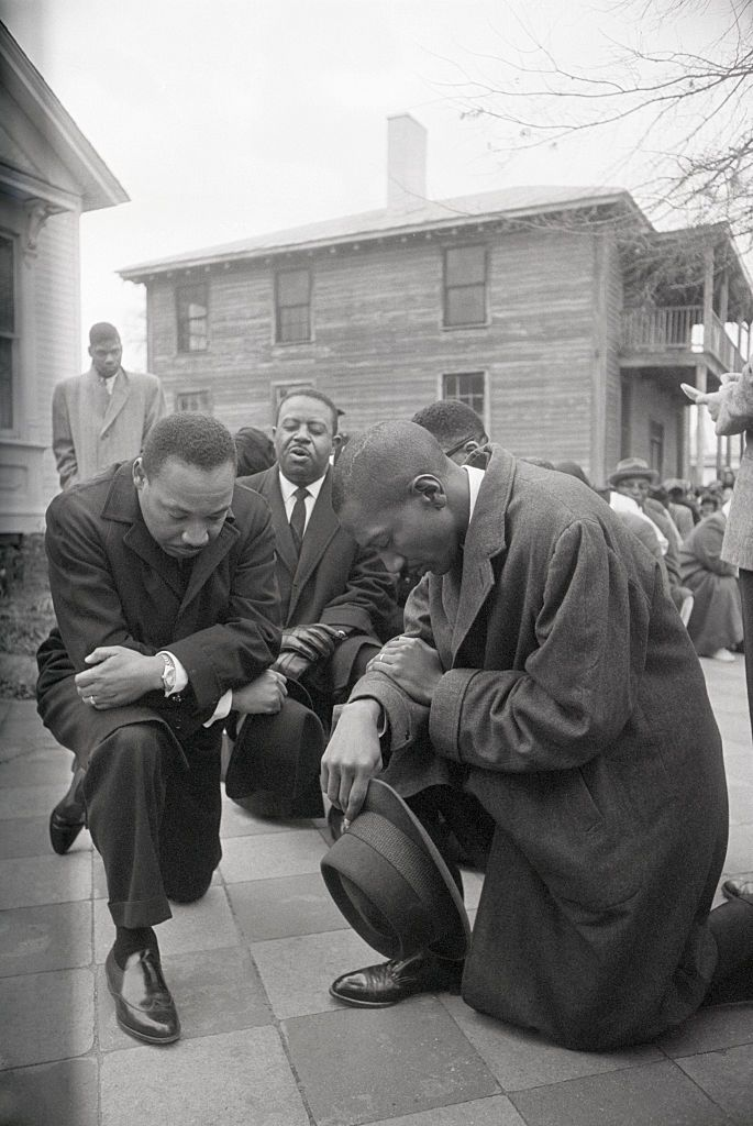 Martin Luther King Jr kneeling outside a courthouse in Alabama