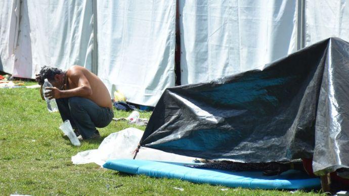 Hombre de la caravana de migrantes echándose agua en la cabeza