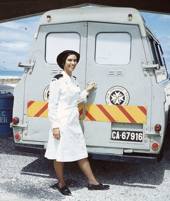 Margaret, vestida con su uniforme de enfermera, frente a una ambulancia del hospital St.John's.