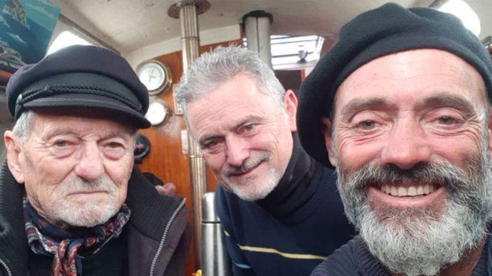 Juan Manuel Ballestero en su barco, el Skua, con su padre y su hermano.