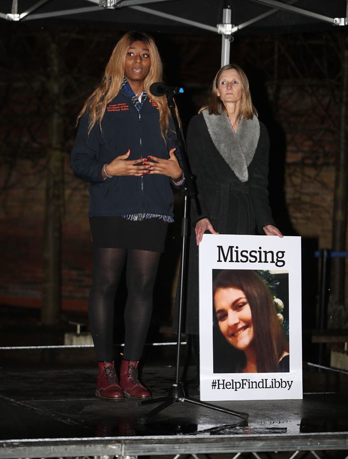 Two women on a stage with one holding a missing Libby Squire placard