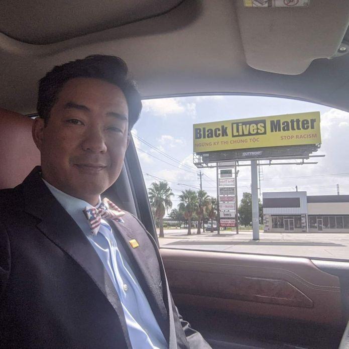 Ông Lê Hoàng Nguyên hãnh diện bên tấm bảng chuyển tải thông điệp của mình