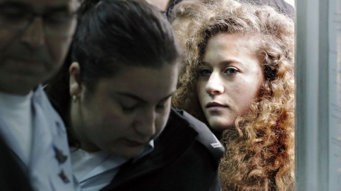 Palestinian teenager Ahed Tamimi enters a military court at Ofer prison, near the West Bank city of Ramallah, on 13 February 2018