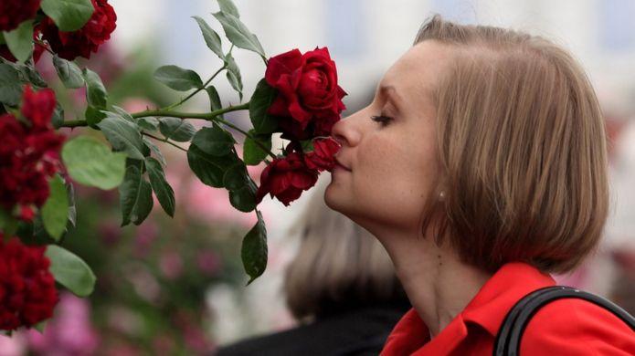 Mujer huele rosas.