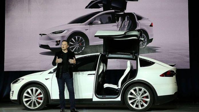 Elon Musk da una conferencia con un Tesla detrás