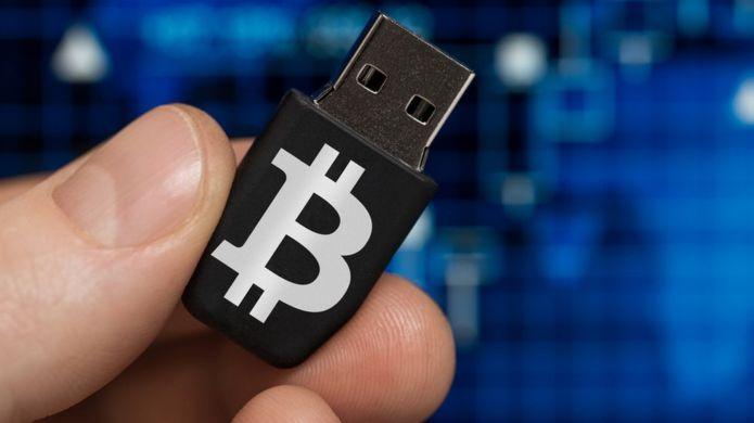 Hombre sosteniendo USB con el logo de bitcoin.