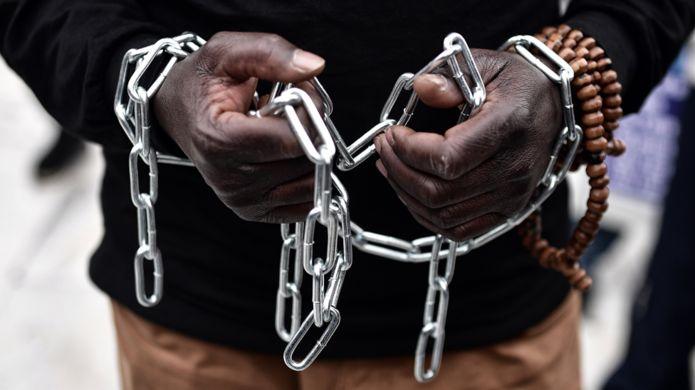 Un migrante africano con sus manos encadenadas participa en una marcha hacia las oficinas centrales de la Unión Europea en Atenas, Grecia, en 2 de diciembre, en protesta por la situación de esclavismo a la que son sometidos muchos en Libia. (Foto: LOUISA GOULIAMAKI)