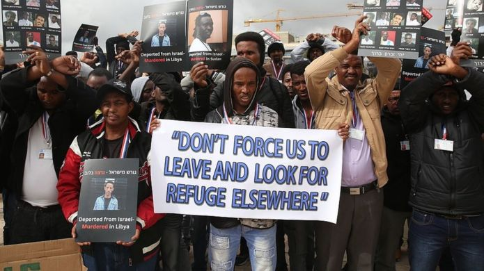 African asylum seekers, mostly from Eritrea, who entered Israel illegally during the past years, hold placards showing migrants who they say were killed after being deported to their country, during a protest against Israel's deportation policy in front of the Supreme Court in Jerusalem on January 26, 2017.