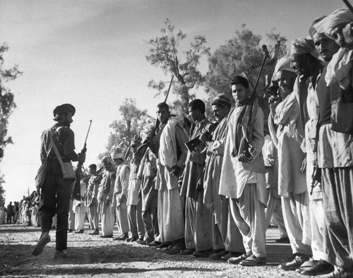 In this 1947 picture, armed Pathan tribesmen wait on the road between Peshawar and Rawalpindi for their leader Batcha Gul, of the Mohman tribe, to arrive with trucks and extra ammo, and lead them into battle in Kashmir.