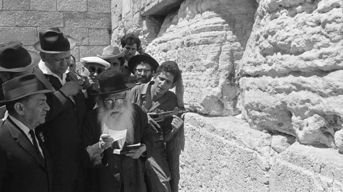A group of Jews pray beside the Wailing Wall.