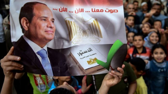 """An Egyptian man holds up a banner saying: """"Vote with us... now... now"""" at a polling station in Menoufia (22 April 2019)"""