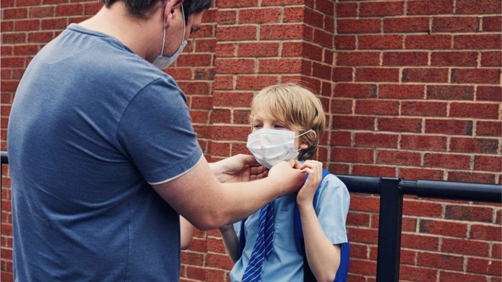 Child being helped with face covering outside school
